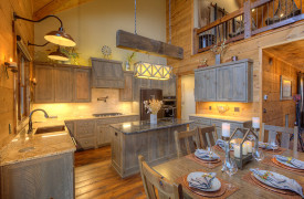 A Rustic Elegant Retreat | Blue Ridge Luxury Cabin Rentals | Cabin Rentals of Georgia | Gourmet kitchen w/ stainless steel appliances, breakfast bar, custom cabinets, beautiful accessories