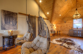 A Rustic Elegant Retreat | Blue Ridge Luxury Cabin Rentals | Cabin Rentals of Georgia | Swinging chairs in loft overlooking layered Mountain View