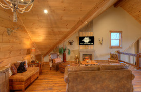 A Rustic Elegant Retreat | Blue Ridge Luxury Cabin Rentals | Cabin Rentals of Georgia | Spacious loft with TV, fireplace, and swinging chairs overlooking Mountain View