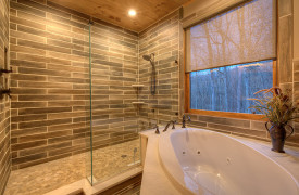 A Rustic Elegant Retreat | Blue Ridge Luxury Cabin Rentals | Cabin Rentals of Georgia | King master ensuite bath with stone shower and jetted tub overlooking mountain views