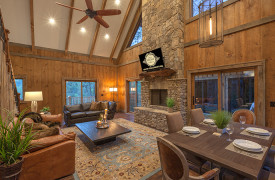 A Mayfly Lodge & Treehouse | Cabin Rentals of Georgia | Living Area with stone fireplace and TV w/ leather furnishings