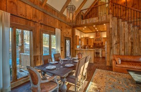 A Mayfly Lodge & Treehouse | Cabin Rentals of Georgia | Luxurious Dining with floor length windows to landscaped front yard