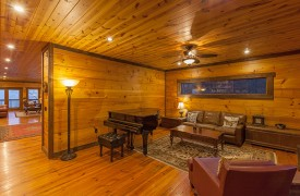 The River's Edge | Cabin Rentals of Georgia | Front Living Room w/ Piano, Leather Furnishings, Bookshelves