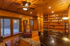 The River's Edge | Cabin Rentals of Georgia | Front Living Room w/ Leather Furnishings and Bookshelves, Piano