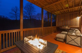 The River's Edge | Cabin Rentals of Georgia | Main Level Porch w/ Fire Table and Comfy Seating Overlooking Toccoa River