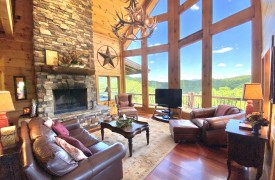 Outlaw Ridge | Cabin Rentals of Georgia | Living Area w/ 2 story glass windows, leather furnishings, fireplace, and TV