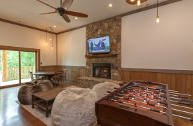 A Mayfly Lodge & Treehouse | Cabin Rentals of Georgia | Terrace Level Game Room with foosball, fireplace and TV and bean bag chairs