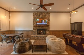 A Mayfly Lodge & Treehouse | Cabin Rentals of Georgia | Terrace Level with gas log fireplace, TV, foosball, game table and two fur bean bag chairs